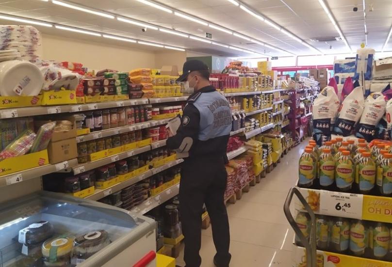 عناصر من شرطة البلدية تراقب المنتجات في أحد محلات الماركت