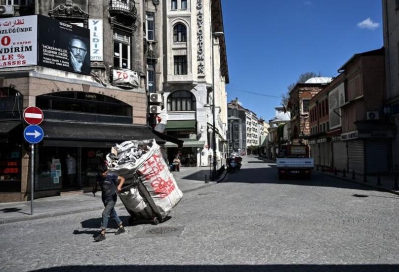 جامع قمامة يسير على طول شارع مهجور في منطقة إمينونو بإسطنبول